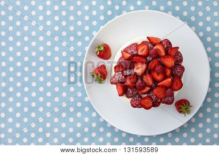 Tart with strawberries, raspberries and cream on blue dotted background. Top view.