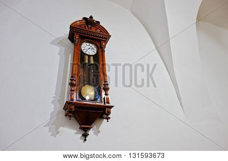 Vintage antique wood clock on white wall