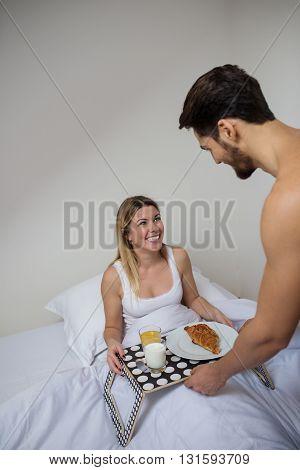 Man bringing his girlfriend breakfast in bed.