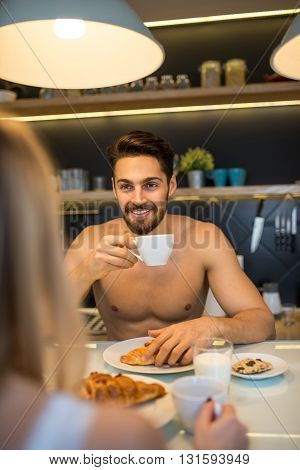 Couple enjoying coffee and breakfast at home.