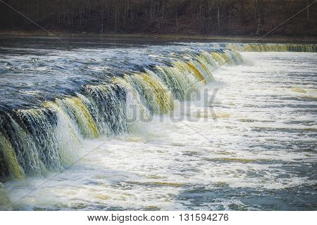 Waterfall in river in early spring .