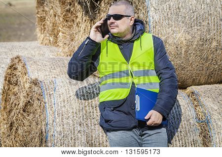 Farmer with smartphone and folder near the hay bales
