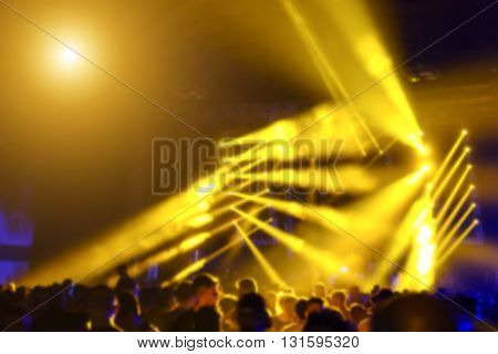 Abstract bokeh with defocused background of laser show in modern disco party night club - Concept of nightlife with music and entertainment - Image with powered colored halos and vivid yellow lights