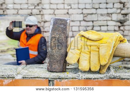 Sledgehammer and gloves on brick wall .