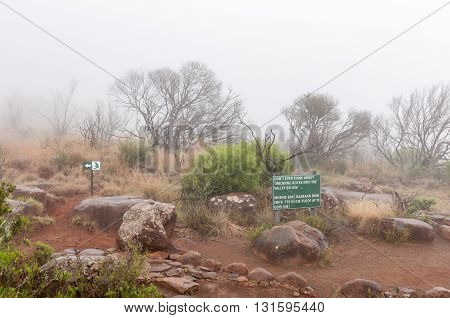 A warning sign and route marker in thick fog on the Crag Lizard trail near the Valley of Desolation viewpoint