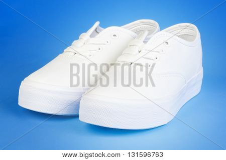 Flatform Plimsolls in white on blue .