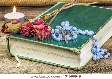 Rosary, bible, rose on the table .