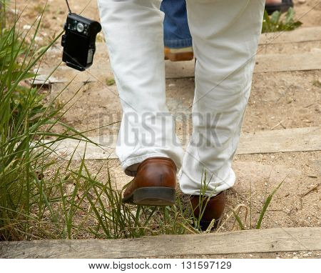 Male tourist walking outdoors on stairs in summer day