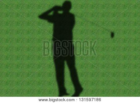 a shadow of golfer in a green fairway