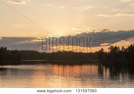 tranquil landscape on wood lake at sunset
