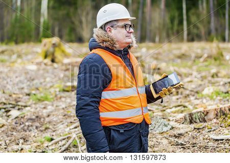 Forest inspector talking on smartphone in clearcutting forest