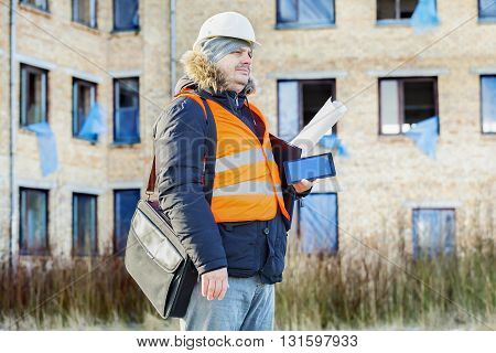 Building inspector with tablet PC near the damaged building