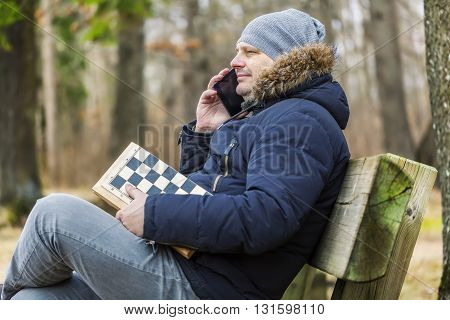 Man with chess talking on smart phone in park