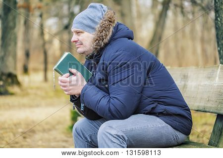 Man with Bible and rosary on bench in the park