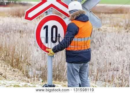 Worker try to fix road sign in autumn day