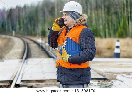 Railroad worker with documentation and smartp hone on railway crossing