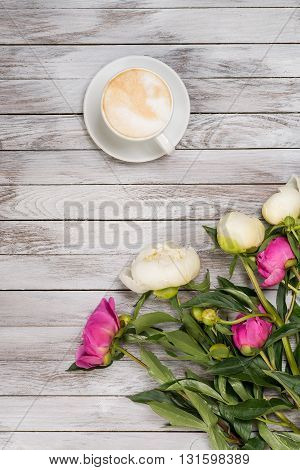 A bouquet of peonies and cup of coffee on the light wooden background. Top view.