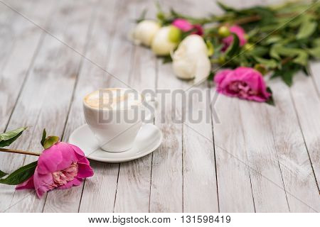 A bouquet of peonies and cup of coffee on light wooden background.