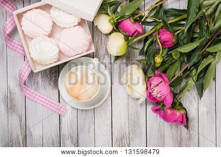 A cup of coffee next to bouquet of peonies, a box with marshmallows and pink ribbon on the wooden background. Top view.