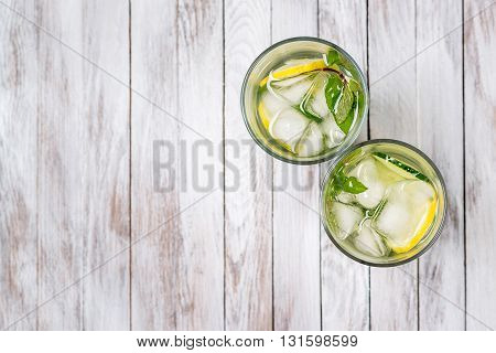 Water with lemon, mint and cucumber on the wooden light background. Water Detox. Top view.