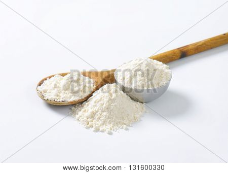 soft wheat flour on wooden spoon and in metal bowl on white background