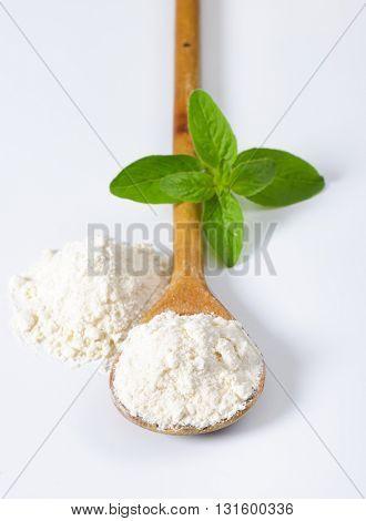 wooden spoon of wheat flour on white background