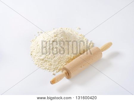 pile of wheat flour and wooden rolling pin on white background