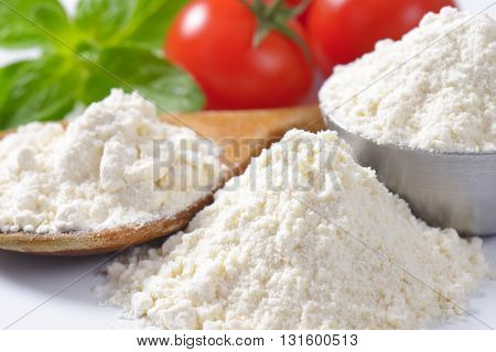 detail of soft wheat flour on wooden spoon and in metal bowl