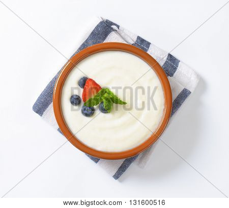 bowl of semolina pudding with fresh fruit on striped napkin