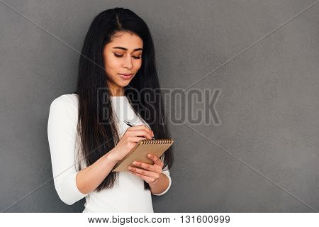 Making some urgent notes. Confident young African woman writing something in her note pad while standing against grey background