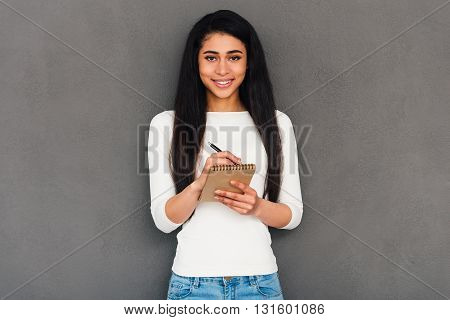 Noting your every word. Confident young African woman holding note pad and looking at camera with smile while standing against grey background