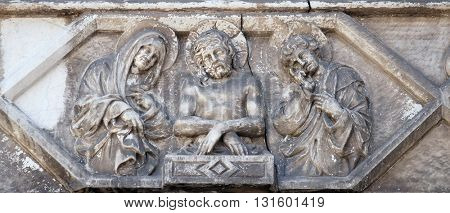 LUCCA, ITALY - JUNE 06, 2015: Jesus bound with the Virgin Mary and St. John on the portal of the Cathedral of S.Martino in Lucca, Italy, on June 06, 2015