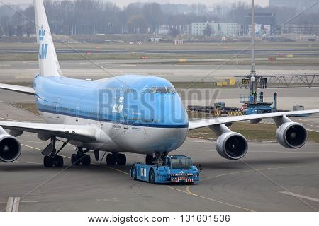 Amsterdam, The netherlands - 15 March , 2015 : Boeing 747 is just arrived at the gate where the passengers leave the aircraftprepared and loaded for a new trip.