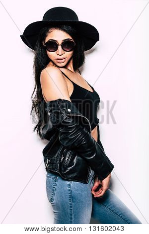 Beautiful seductress. Beautiful young mixed race woman in hat taking off her leather jacket and looking over shoulder while standing against white background