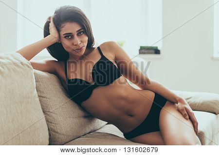 Sweet seductress. Beautiful young mixed race woman in black lingerie looking at camera while sitting on couch at home