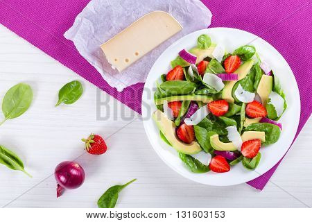 Strawberry baby spinach red onion slices of goat cheese and avocado salad on a white dish on a white wooden background with piece of organic goat cheese on a parchment paper top view