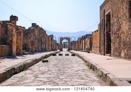 View of the main street of the archaeological site of Pompeii during the day , deserted