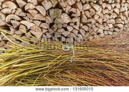 Bundles of brushwood laying in front of a stack of firewood