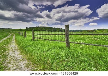 View of spring landscape with road and fence
