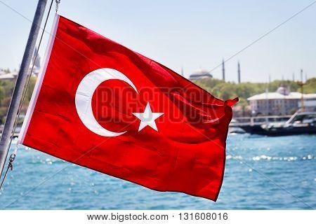 Turkish flag on flagpole against the sea
