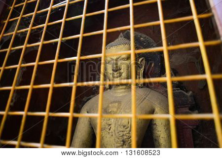 Historic Buddha images in a protective cage at Ananda Temple in Bagan Myanmar