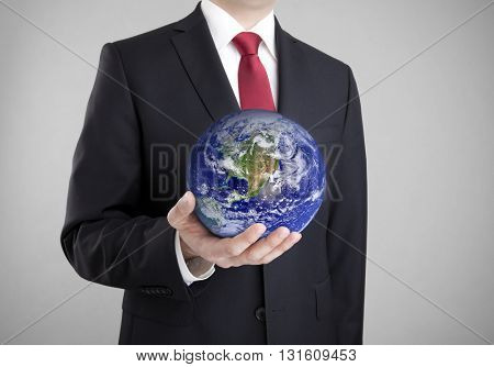 Businessman holding globe. Clipping path included. Earth image provided by Nasa.