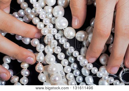 Choosing pearls necklaces and bracelets with magnifying lens