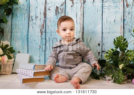 Portrait of the little boy with the books in studio