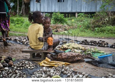 Seghe, Solomon Islands - June 16, 2015: Girl selling mussels and holding baby on the local market.