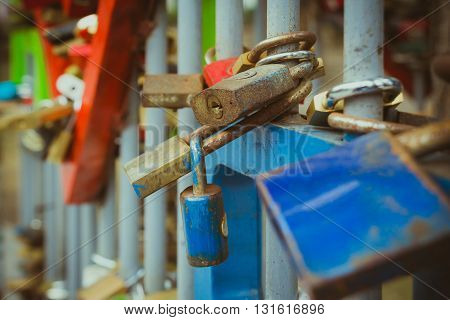 Close up on many love locks on fence.