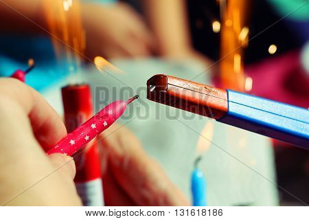 Someone holding pink birthday candle in the hand and light it a with gasoline lighter. In the background there are lighted candles and fireworks.