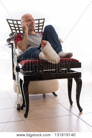 Young Man With A Broken Ankle And A Leg Cast