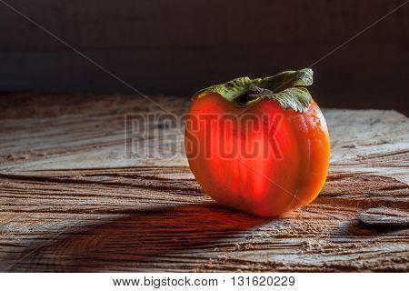 Slice Of Persimmon On Wood
