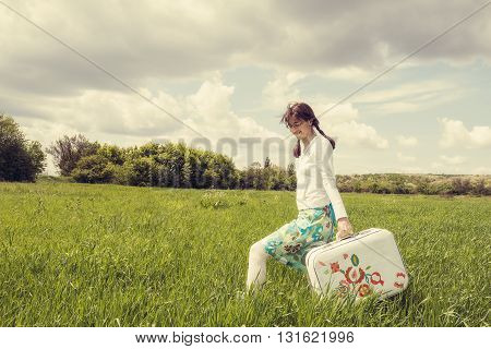 Smiling happily hipster girl goes along the green field with vintage painted suitcase on the background of cloudy sky. Concept-expectation of traveling. Toned image.